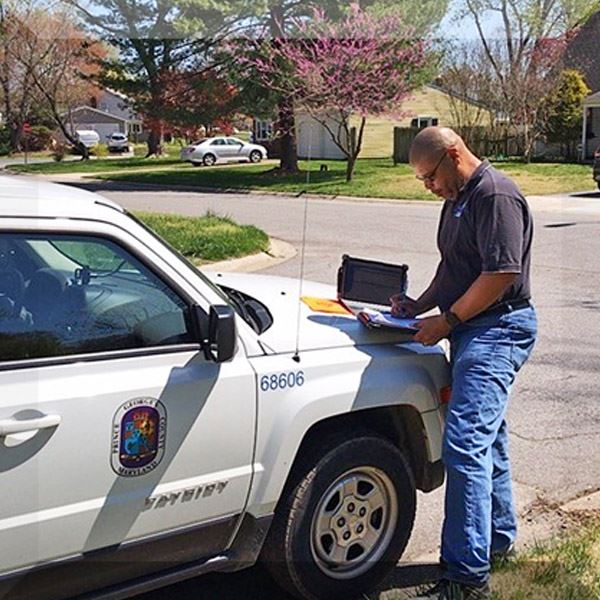 Inspector JS working outside with laptop on the hood of his car