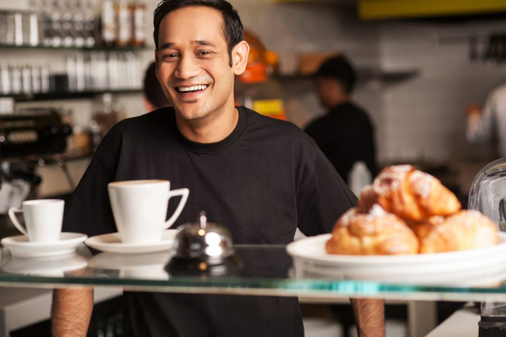 Man Smiling Behind a Food Service Counter
