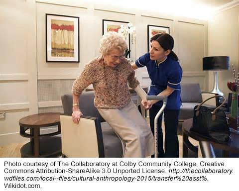 health professional helping elderly woman up from sitting position